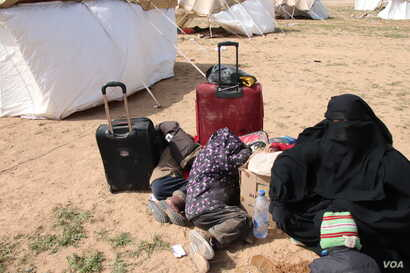 """A woman, not knowing when or where she is going, waits with her children behind a collection of tents. """"I don't know who I'm supposed to be afraid of, but I am afraid,"""" she says, near Baghuz in Deir el-Zour, Syria, Feb. 26, 2019. (H.Murdock/VOA)"""