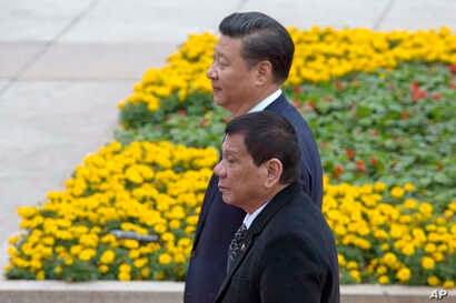 Philippine President Rodrigo Duterte, front, walks with Chinese President Xi Jinping during a welcome ceremony outside the Great Hall of the People in Beijing, China, Oct. 20, 2016.