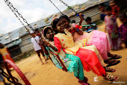 Rohingya refugee children ride on a swing ride on the day of Eid al-Adha in the Kutupalong refugee camp in Cox's Bazar, Bangladesh, Aug. 22, 2018.