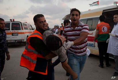 Palestinian medics carry a wounded man into a field clinic after being shot by Israeli troops during a protest at the Gaza Strip's border with Israel, July 20, 2018. Israel carried out airstrikes and deployed tanks at militant sites in Gaza killing f...