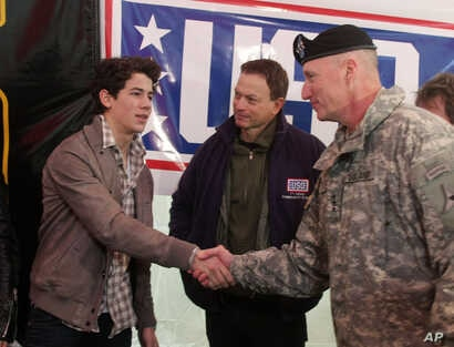 FILE - Fort Hood commander Lt. Gen. Robert Cone, right, greets singer Nick Jonas, left, as actor Gary Sinise looks on at a USO Community Strong event in Fort Hood, Texas.