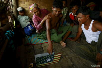 Abdhulami (C), 22, who was released from a human trafficking boat, points at pictures of people he recognises from the boat as he rests at a refugee camp outside Sittwe, Myanmar May 27, 2015. When the Myanmar navy seized the boat used by people smugg...