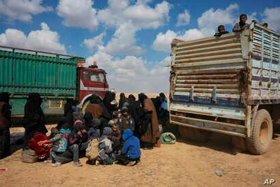 Women and children gather near trucks after being evacuated from the last territory held by Islamic State militants outside Baghuz, Syria, March 6, 2019.