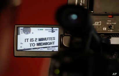 A member of the media films the Doomsday Clock after a news conference at the National Press Club in Washington, Thursday, Jan. 25, 2018, announcing that the Bulletin of the Atomic Scientists has moved the minute hand of the Doomsday Clock to two min...