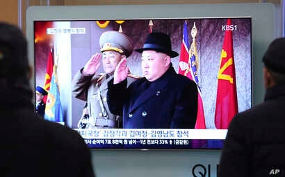 People watch a TV showing North Korean leader Kim Jong Un during a military parade in Pyongyang, North Korea, at Seoul Railway Station in Seoul, South Korea, Feb. 8, 2018.