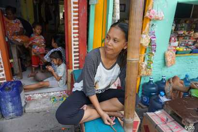 Ina Mariana sits outside a sustainable housing prototype in Kampung Tongkol, Indonesia.