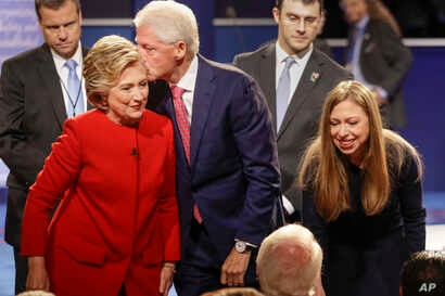 Former President Bill Clinton kisses Democratic presidential nominee Hillary Clinton as she and their daughter, Chelsea Clinton, greet supports during the presidential debate at Hofstra University in Hempstead, N.Y., Sept. 26, 2016.