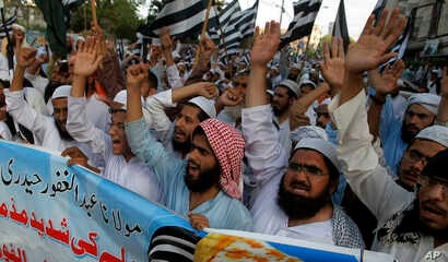 FILE - Supporters of a Pakistani religious group Jamiat-e-Ulema Islam, chant slogans during a demonstration to condemn a suicide bombing the day before, in Karachi, Pakistan, May 13, 2017. The Islamic State group said it carried out the attack on a P...