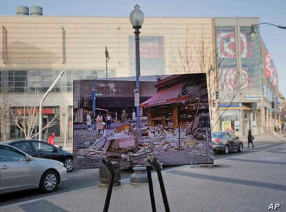 A April 6, 1968, photo of looted and burned buildings is placed on a easel at the present day shopping area near 14th and Kenyon Streets  in northwest Washington, on March 25, 2018.