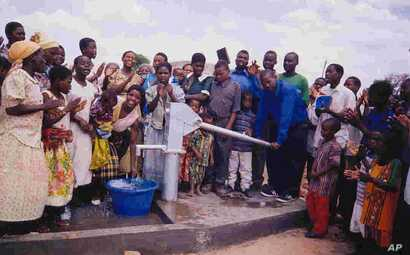 Villagers mark the opening of a new borehole