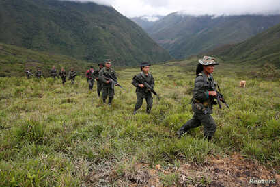 Members of the 51st Front of the Revolutionary Armed Forces of Colombia (FARC) patrol in the remote mountains of Colombia, Aug. 16, 2016.