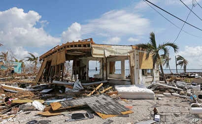 FILE - Debris surrounds a destroyed structure in the aftermath of Hurricane Irma in Big Pine Key, Fla. Rising sea levels and fierce storms have failed to stop relentless population growth along U.S. coasts in recent years, a new Associated Press anal...