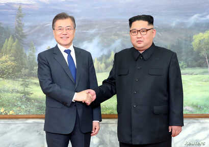 South Korean President Moon Jae-in shakes hands with North Korean leader Kim Jong Un during their summit at the truce village of Panmunjom, North Korea, May 26, 2018.