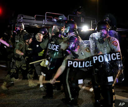 A man is detained after a standoff between protesters and police Monday, Aug. 18, 2014.