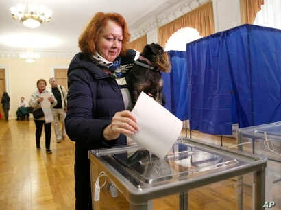 A woman holds a pet and casts her ballot at a polling station during the presidential election in Kyiv, Ukraine, March 31, 2019.
