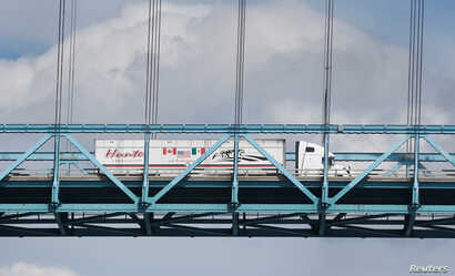 A commercial truck with a Canada, United States and Mexico flag on its side is seen crossing over the Ambassador Bridge into Windsor, Ontario from Detroit, Michigan U.S. Aug. 29, 2018.
