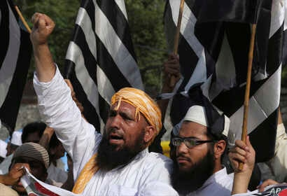 FILE - Supporters of Jamiat-e-Ulema Islam, a Pakistani religious group, chant slogans during a demonstration to condemn a suicide bombing, in Lahore, Pakistan, May 14, 2017. The Islamic State group said it orchestrated a suicide attack on Abdul Ghafo...