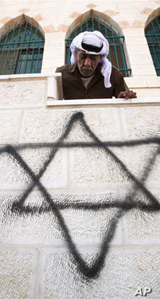 A Palestinian man looks down on graffiti of the Star of David spray-painted on a wall of a West Bank mosque, September 5, 2011.