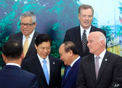 Vietnamese Prime Minister Nguyen Xuan Phuc (center right) shakes hands with Chinese Minister of Commerce Zhong Shan (center left) as Philippine Trade Secretary Ramon Lopez (top left)  U.S Trade Representative Robert Lighthizer (top right) and Peruvia...