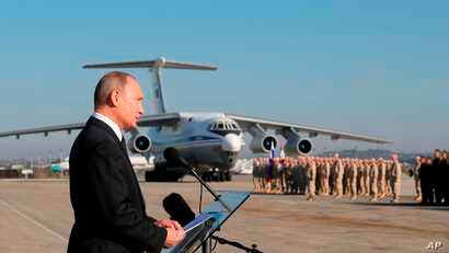 FILE - Russian President Vladimir Putin addresses the troops at the Hemeimeem air base in Syria, Dec. 12, 2017. U.S. President Donald Trump recently shocked advisers in declaring an intention to withdraw troops from Syria. Now, apparently angered by ...