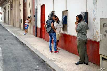 Cubans use payphones on Consulado side street across from Havana's Capitol building.