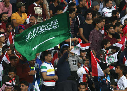 FILE - A football fan waves a Saudi Arabian flag during the friendly football match between Iraq and Saudi Arabia at a city stadium in Basra, Feb. 28, 2018.