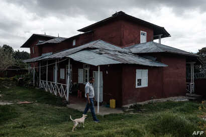 FILE - Berhanu Mengistu walks his dog in front of his family house which has been protected as a historic house by the tourism bureau in Addis Ababa, Nov. 29, 2018.