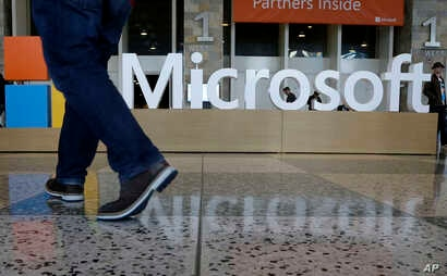 FILE - A man walks past a Microsoft sign set up for the Microsoft BUILD conference at Moscone Center in San Francisco, April 28, 2015. Microsoft says it's requiring its U.S. suppliers to offer their employees at least 12 weeks paid leave to care for