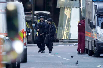 Armed British police officers walk within a cordoned off area after an attack at the London Bridge, June 4, 2017. Police said that late Saturday a vehicle mowed down pedestrians on London Bridge and men with large knives stabbing passersby at nearby