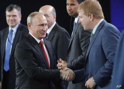 Russia's President Vladimir Putin (left) shakes hands with Myron Brilliant, executive vice president and head of International Affairs at the U.S. Chamber of Commerce, at the St. Petersburg International Economic Forum in St. Petersburg, Russia, June...