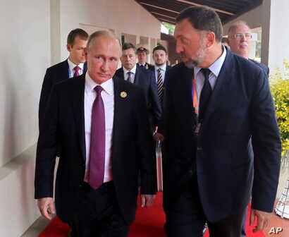Russia's President Vladimir Putin, left, and Russian metals magnate Oleg Deripaska, right, walk to attend the APEC Business Advisory Council dialogue in Danang, Vietnam, Nov. 10, 2017.