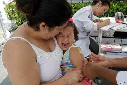 In this March 2, 2018 photo, a child cries out as she is given a vaccine against yellow fever at a public health post set up on the outskirts of Sao Paulo, Brazil.