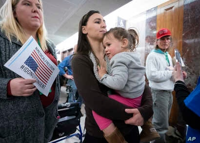 Sarah Myriam of New Jersey holds her daughter Aliyah, 2, as they join activists opposed to vaccinations outside a Senate Health, Education, Labor and Pensions Committee hearing on Capitol Hill in Washington, March 5, 2019.