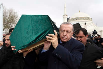 Turkey's President Recep Tayyip Erdogan, center, carries a coffin as he joins hundreds of mourners who attend the funeral prayers for nine members of Alemdar family killed in a collapsed apartment building, in Istanbul, Saturday, Feb. 9, 2019.