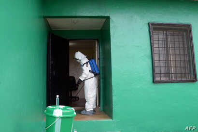 A health worker, wearing a protective suit, disinfects a house during an Ebola prevention drill at the port in Monrovia, Liberia, Aug. 29, 2014.