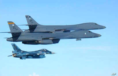 In this photo released by Japan Air Self Defense Force, U.S. Air Force B-1B bombers, top, fly with a Japan Air Self Defense Force F-2 fighter jet over Japan's southern island of Kyushu, just south of the Korean Peninsula, during a Japan-U.S. joint ex...