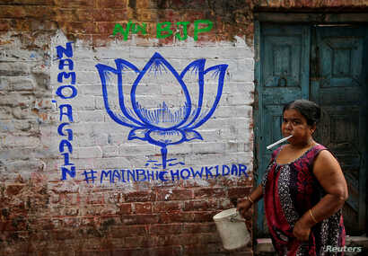 FILE - A woman walks past a wall painted with the election symbol of India's ruling Bharatiya Janata Party (BJP) in an alley at a residential area in Kolkata, India, March 22, 2019.