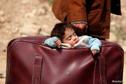 A child sleeps in a bag in the village of Beit Sawa, eastern Ghouta, Syria March 15, 2018.