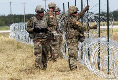 U.S. Army soldiers from Ft. Riley, Kansas, put up barbed wire fence for an encampment to be used by the military near the U.S. Mexico border in Donna, Texas, U.S., November 4, 2018.