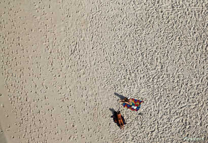 An aerial view shows people on Barra da Tijuca beach in Rio de Janeiro, Brazil, July 16, 2016.
