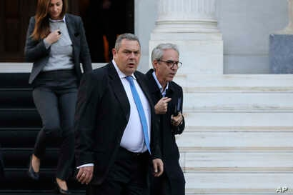 Greek Defense Minister Panos Kammenos leaves Maximos mansion following a meeting with Greece's Prime Minister Alexis Tsipras, in Athens, Jan. 13, 2019.
