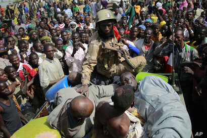 A Malian soldier pushes suspected Islamist extremists into the back of an army truck in Gao, Mali, January 29, 2013.