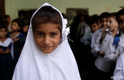 FILE - A girl attends morning assembly at the Mashal Model school in Islamabad, Pakistan, Sept. 29, 2017.