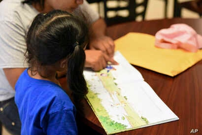 FILE - In this photo provided by U.S. Immigration and Customs Enforcement, a child looks at a book at South Texas Family Residential Center in Dilley, Texas, Aug. 9, 2018.