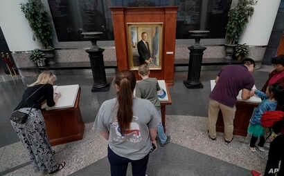 Visitors to the George H.W. Bush Presidential Library and Museum sign condolence books, Dec. 1, 2018, in College Station, Texas.