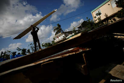 Carlos Ventura carries a corrugated metal sheet to be used for a ceiling, while he helps a neighbour to rebuild her house, which was partially destroyed by Hurricane Maria.