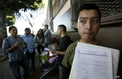 FILE - Illegal immigrant Layios Roberto waits outside the offices of Coalition for Humane Immigrant Rights in Los Angeles, Aug. 15,  2012.