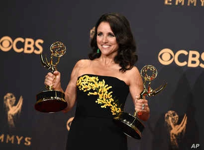 """Julia Louis-Dreyfus poses in the press room with her awards for outstanding lead actress in a comedy series and outstanding comedy series for """"Veep"""" at the 69th Primetime Emmy Awards, Sept. 17, 2017, at the Microsoft Theater in Los Angeles."""