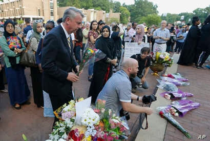 Republican gubernatorial candidate, Ed Gillespie, front left, waits to place a flower on an impromptu memorial for Nabra Hassanen, who was killed over the weekend in a road rage incident, prior to the start of a vigil in honor of Nabar on Wednesday, ...