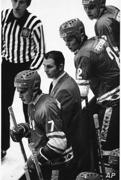 Soviet Coach Victor Tikhonov  is framed by Soviet players Aleksei Kasatonov (7) and Viacheslav Fetisof, as the last minute counts down in the USA vs USSR ice hockey game in Lake Placid, N.Y. during the Winter Olympic Games on Feb. 22, 1980.
